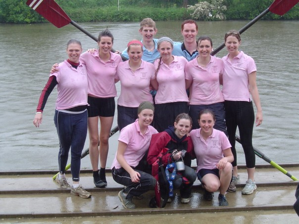 Hertford women's rowing crew stood next to the river with a set of oars