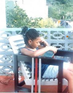 Jasmine Richards as a child, sat outside reading