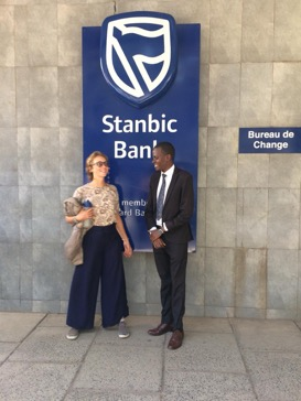 Michelle stood with a man next to a sign for 'Stanbic Bank'