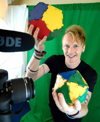 Tm Crawford holding multi-coloured three dimensional shapes in front of a camera, with a green-screen behind him