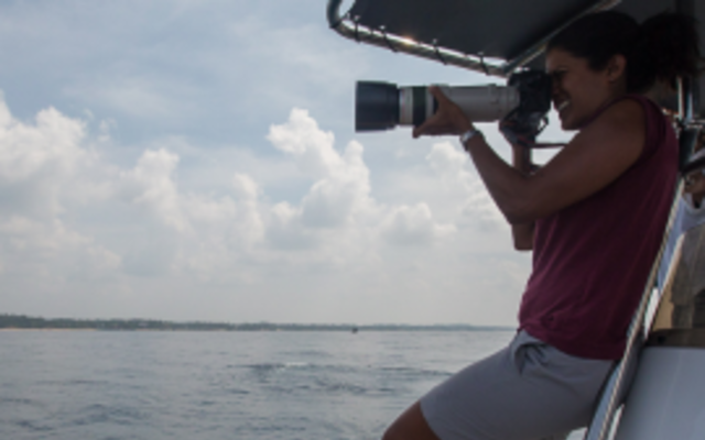 Asha de Vos stood on a boat, using a camera