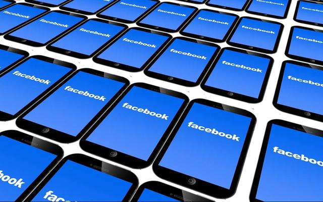 Many mobile devices, stretching off the edge of the image in all directions, all showing the Facebook logo