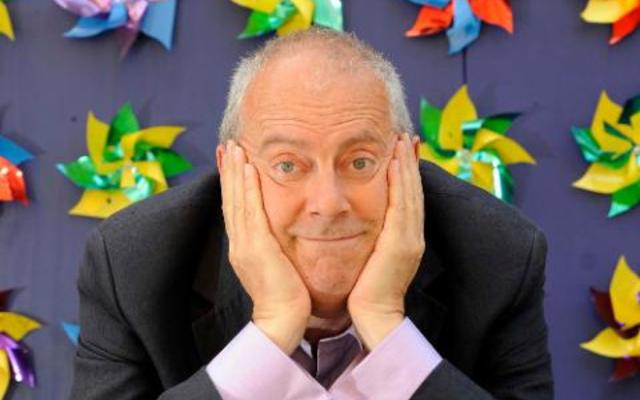 Gyles Brandreth, with his chin on his hands, in front of a wall of colourful windmills