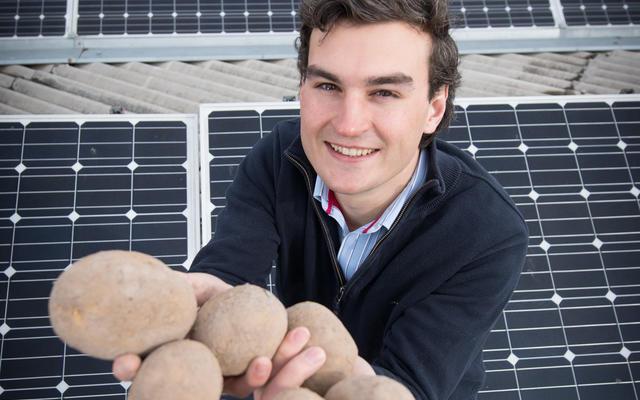 Josh Burton stood amongst solar panels, holding potatoes