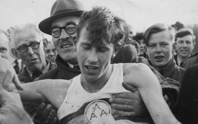 An exhausted Roger Bannister is held up by supporters