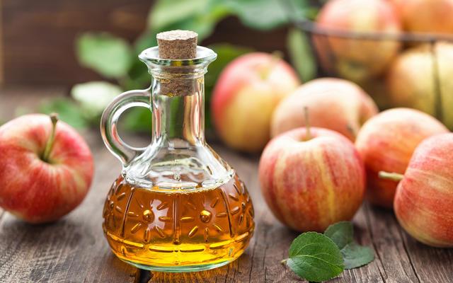 Bottle of cider amidst apples