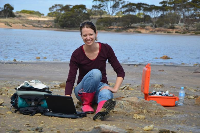 Bethany Elhmann with a laptop and equipment, working on the beach of a lake