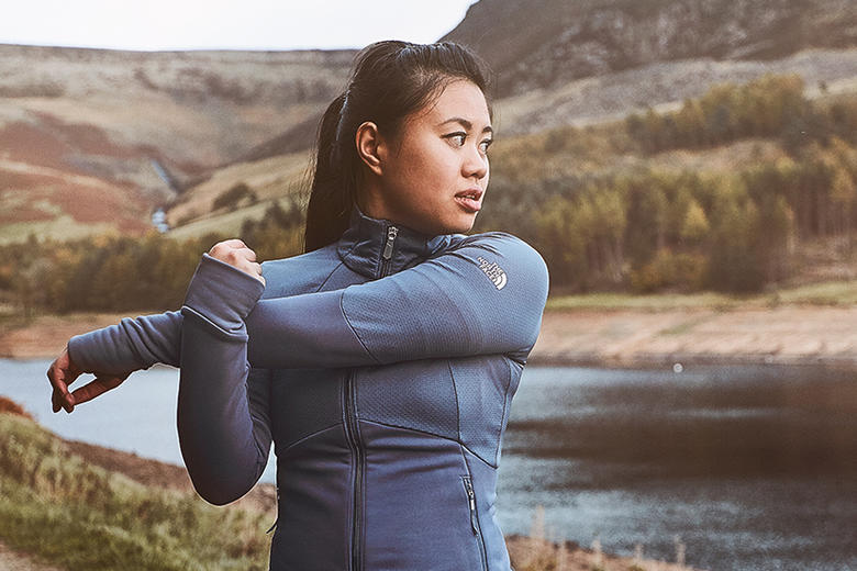 Katie Myint stretching her upper arm, whilst stood next to a river in a mountainous, rural setting