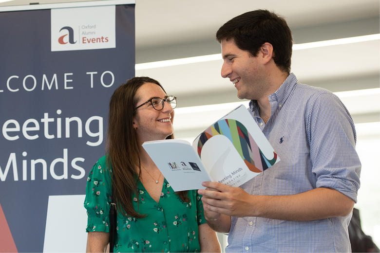 Two attendees looking at a brochure in front of a Meeting Minds pull-up banner
