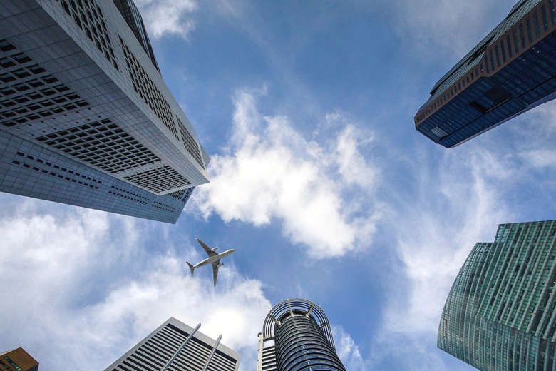 A view from groundlevel vertically upwards through skyscrapers, with an aeroplane flying above them
