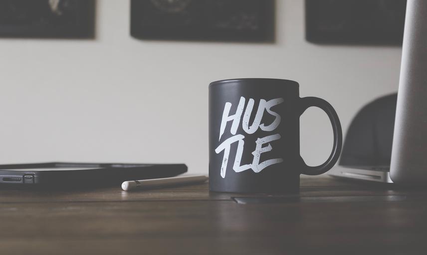 Coffee mug on table reading hustle