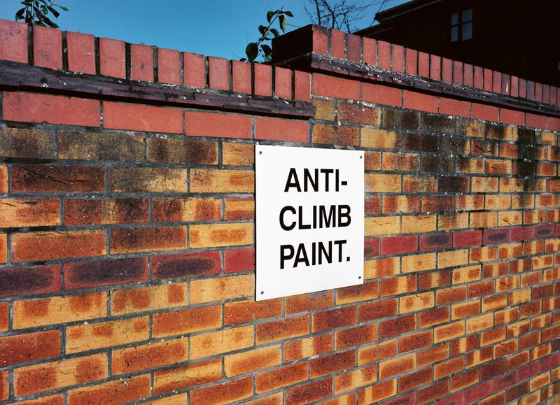 Brick wall with sign 'Anti-Climb Paint'