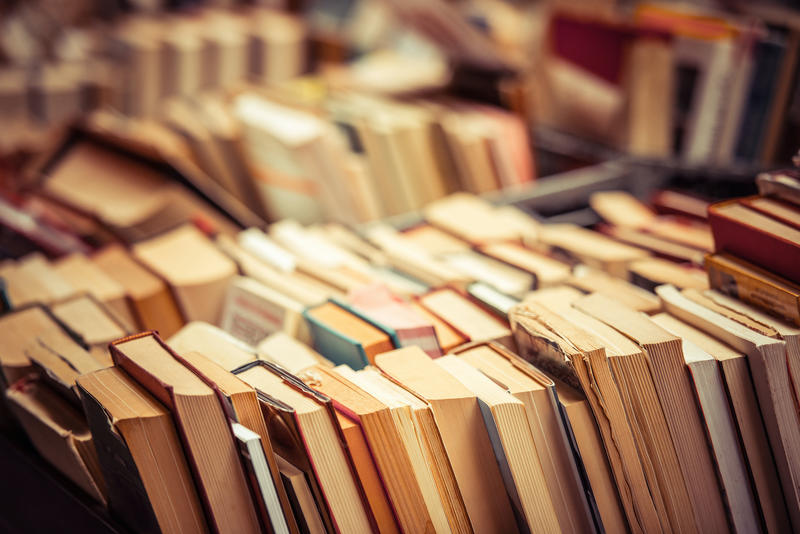 Used books piled up across a table