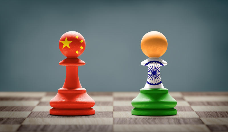 Two chess pawns - one is painted in the colours of the flag of the China, the other in the colours of the flag of India