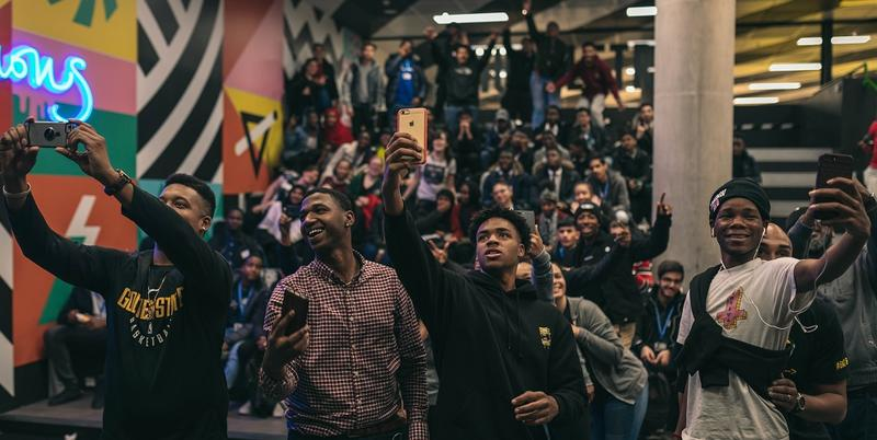 Four black students taking selfies at an exhibition with a large group behind them, posing for the selfie