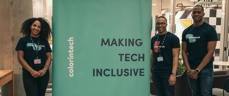 Three members of the colorintech team stood next to a banner which reads 'colorintech' and 'Making tech inclusive'