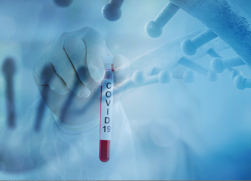A hand holding a test tube labelled 'covid 19', with a close up of a virus faded in the background of the picture