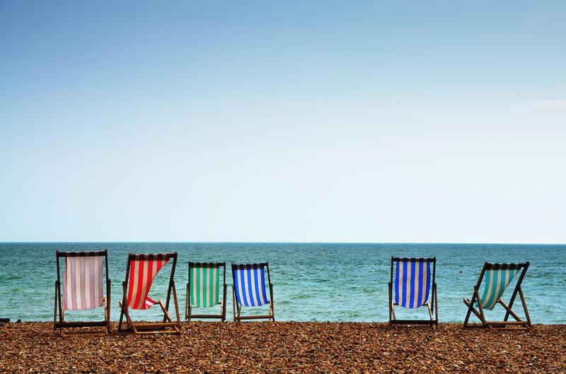 A row of six deckchairs on a shingle beach, pointing towards the sea