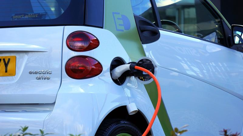 A close up picture of the back of an electric car, with the charging cable going in
