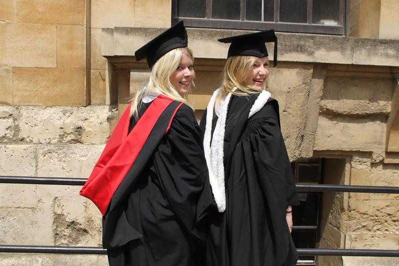 Emma Yandle with a friend, both in graduation gowns and caps, walking through Oxford