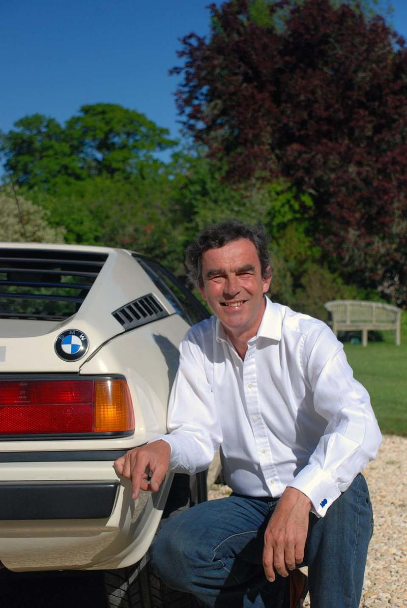 Eric Verdon Roe crouched at the rear of a white BMW M1