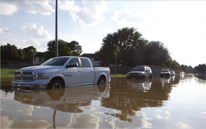A street of parked cars, with flood water almost covering the wheels