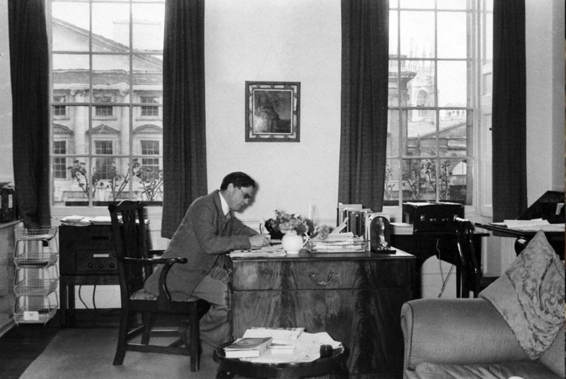 A blacl and white picture of Hugh Trevor Roper working at a desk, with part of Christ Church college visible through the window behind him