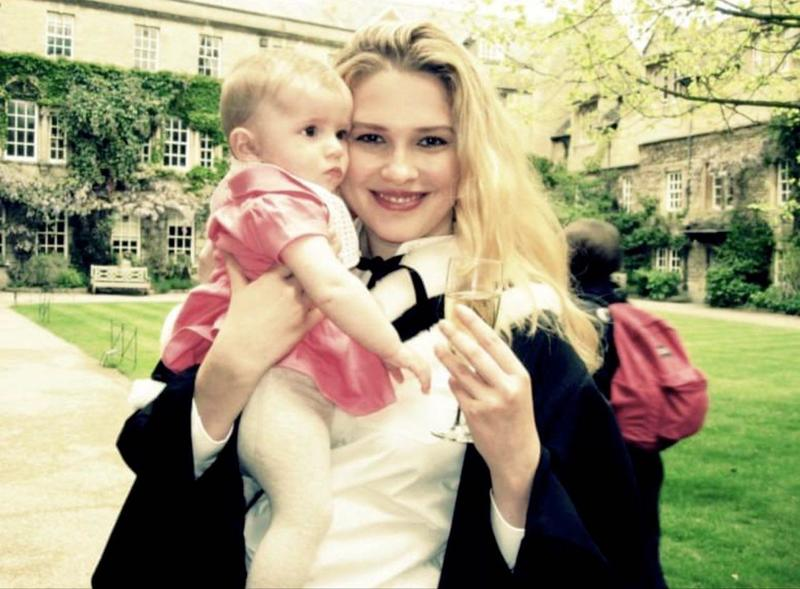 Irra Ariella Khi after her graduation ceremony, stood in a college quad, holding a baby