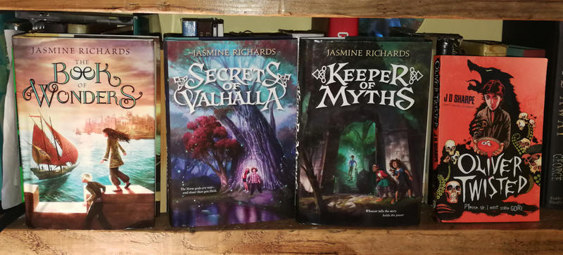 A display of three books by Jasmine Richards - The Book of Wonders, Secrets of Valhalla, Keeper of Myths - next to Oliver Twisted by JD Sharpe
