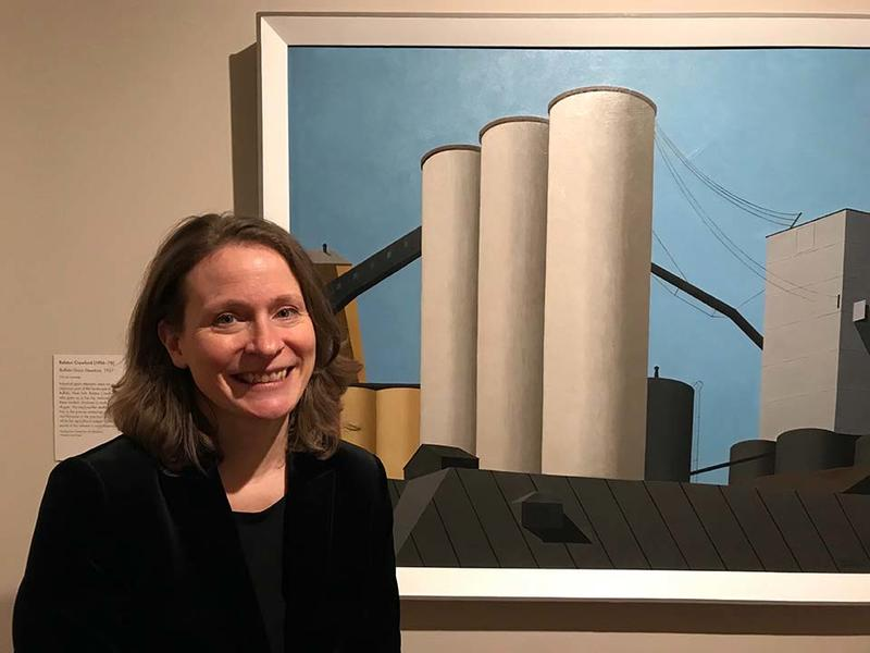 Dr Katherine Bourguignon stood in front of the painting Buffalo Grain Elevators by Ralston Crawford