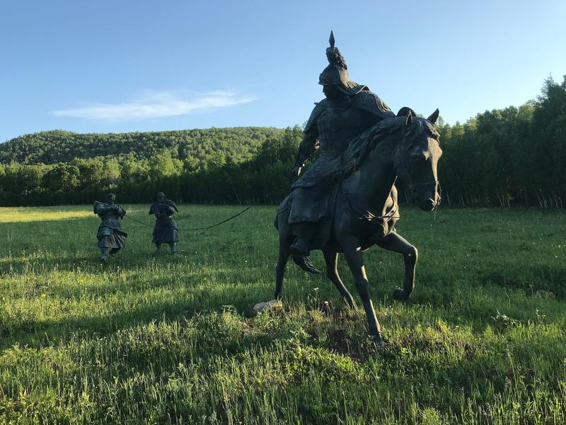 A picture of a statue of Yesugei, Genghis's father, returning home - it is two people being led across a field by a man on horseback