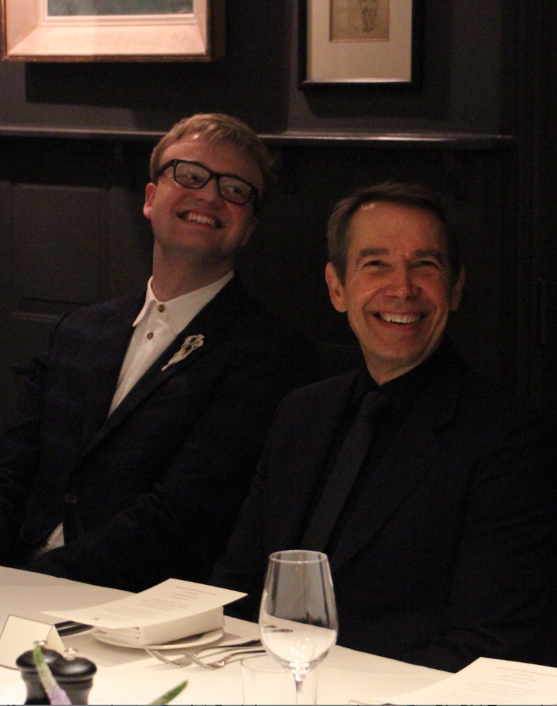 Oli Lloyd-Parry and Jeff Koons, seated at a dining table