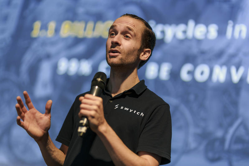 Oliver Montague speaking while holding a micrphone