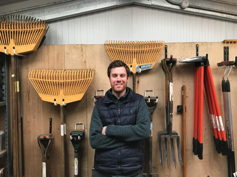 Patrick Green stood in front of a wall on which garden tools are mounted