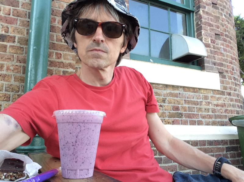 Phil sat at a table, with a purple drink, bruises visble on his right upper arm