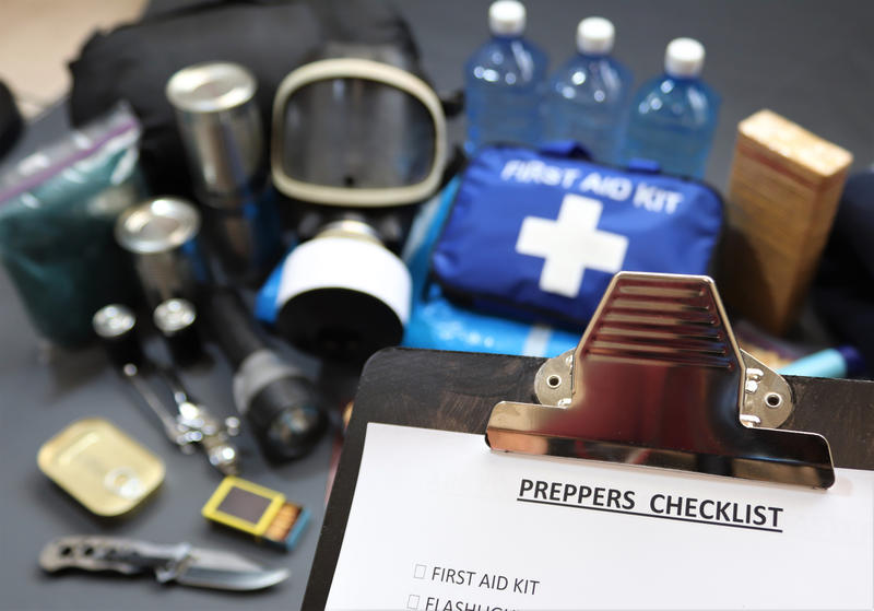 In the foreground is a clipboard with a title 'Preppers checklist', and in the background are various items including medical supplies, water, torch and knife