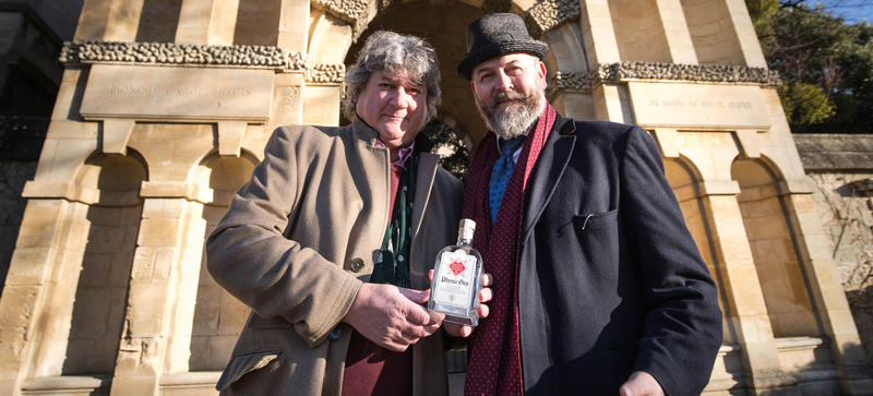 Professor Simon Hiscock and Tom Nicolson holding a bottle of Physic Gin in Oxford Botanic Gardens