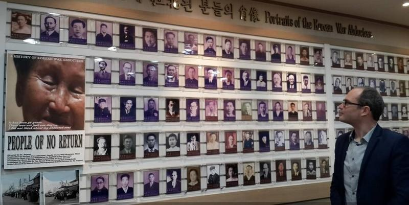 Tarek Cheniti looking at a wall of photos, titled 'Portraits of the Korean War Abductees'