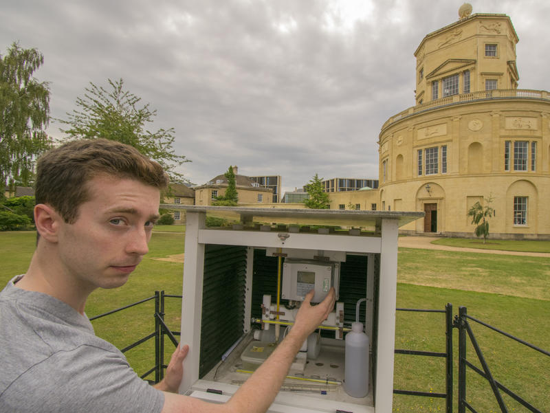 A student using scientific equipment to record the temperature in front of the Radcliffe Observatory in Oxford