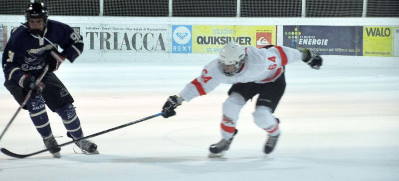 Two ice hockey players - one in white, one in blue - compete for the puck
