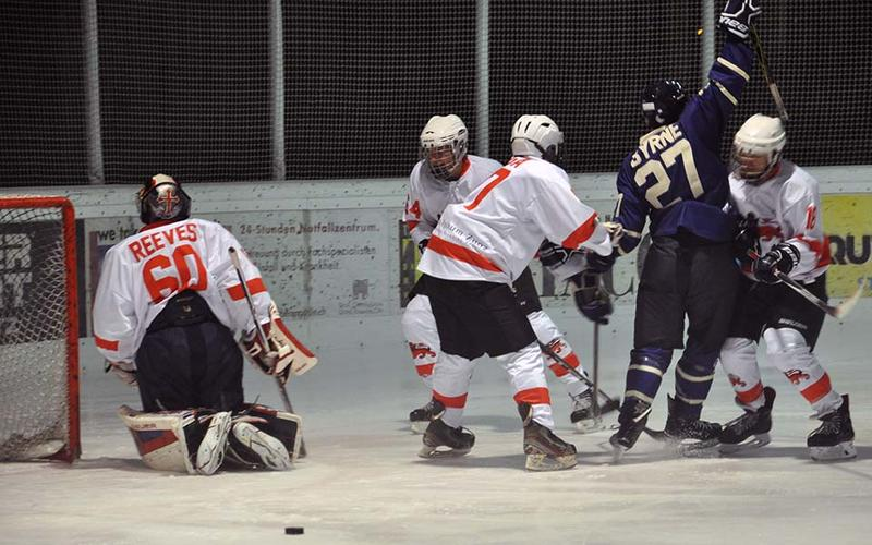 An ice hockey match in progress, and Byrne, number 27, is surrounded by opposing players