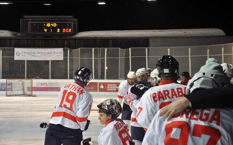 An ice hockey team on a rink, looking disappointed, with a scoreboard showing 4-3 in the background