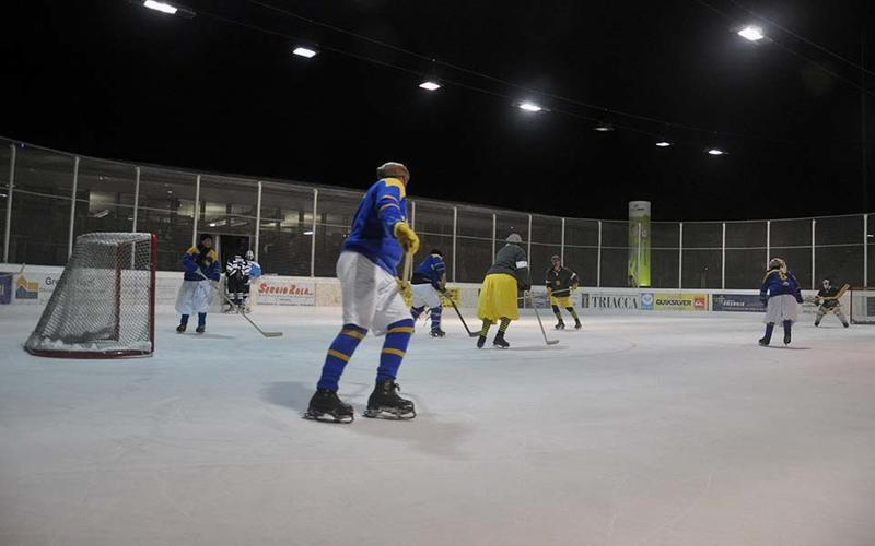 An ice hockey match in progress, with the participants wearing vintage uniforms