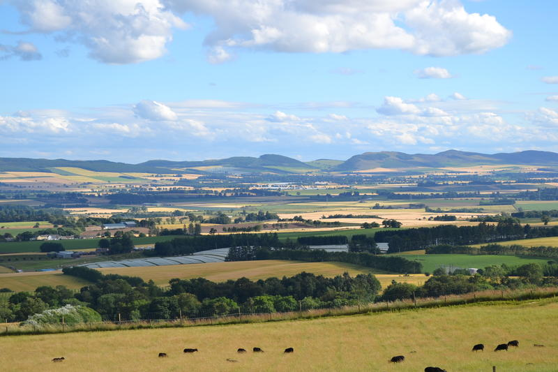 A view from a hill, over farmland toward hills in the distance