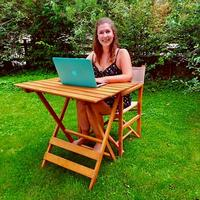 Anna sitting at desk in her garden